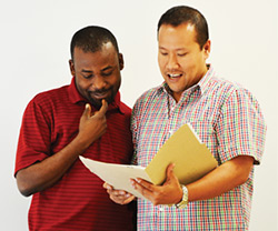 Two smiling men looking at a file