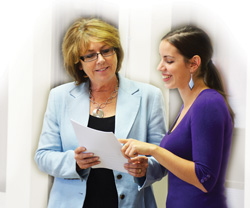 Two smiling women looking over a document